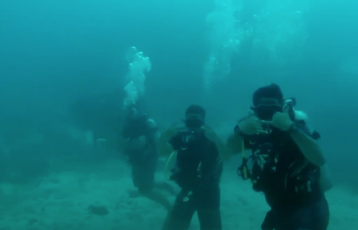 3 Divers Underwater Conducting Research